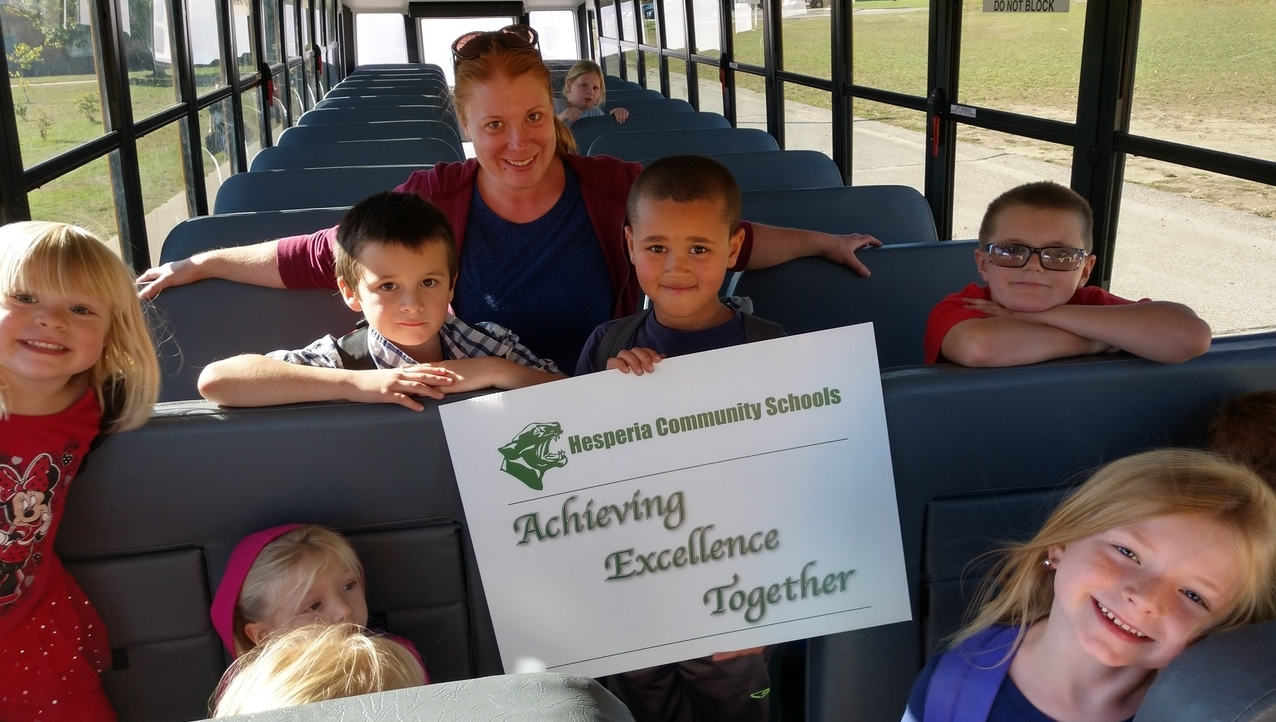 Bus students holding Achieving Excellence Together motto sign.